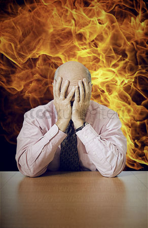 Worry : Depressed senior businessman sitting at desk with fire in background