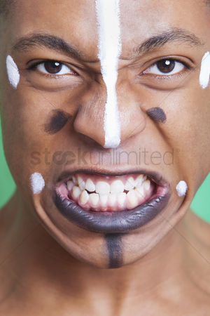 Rage : Detail shot of aggressive mixed race man with painted face clenching teeth