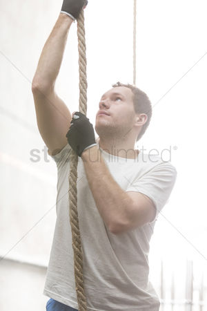 Rope : Determined man climbing rope in crossfit gym