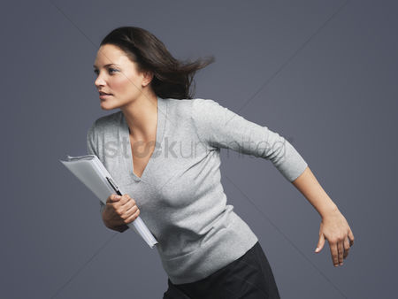 Notebook : Determined young businesswoman leaning into wind