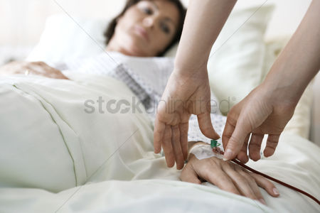 Hand : Doctor attaching intravenous tube to hand of patient close up of hands