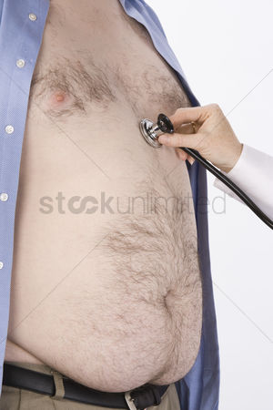 Heart : Doctor hand with stethoscope on overweight man s heart mid section