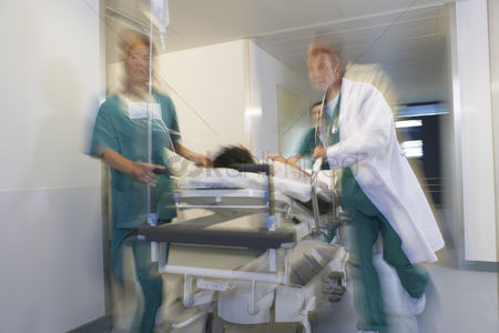 Health : Doctors running patient on gurney through hospital corridor motion blur