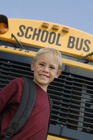 Schoolkids : Elementary student standing by school bus