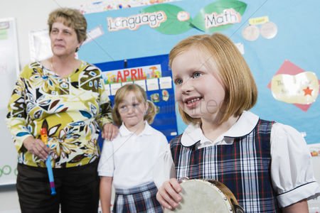 Schoolkids : Elementary student with tambourine in music class