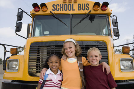 Friends : Elementary students standing by school bus