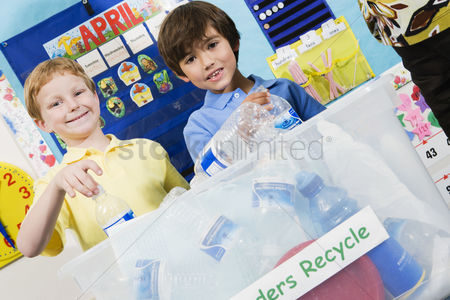 Posed : Elementary students with recycling container