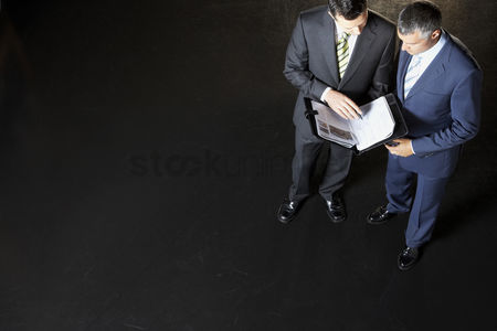 Business suit : Elevated view of two businessmen reading documents against dark background