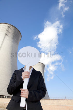 Demonstration : Engineer in front of cooling towers with sign