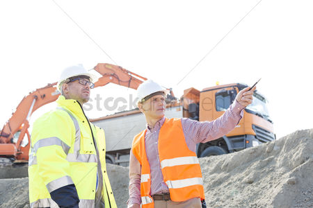 Supervisor : Engineer showing something to colleague while discussing at construction site against clear sky
