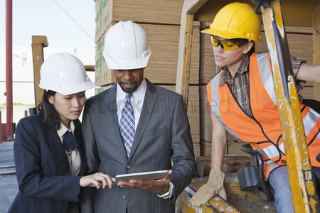 Businesswomen : Engineers and female industrial worker looking at tablet pc