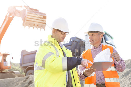 Supervisor : Engineers discussing over documents at construction site