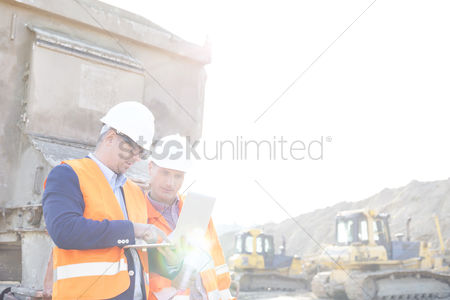 Supervisor : Engineers using laptop at construction site against clear sky