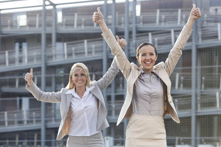 Employee : Excited young businesswomen gesturing thumbs up against office building