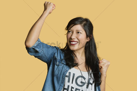 Jacket : Excited young woman with raised fist while looking away over colored background
