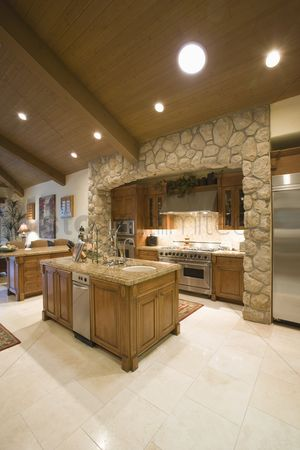 High ceiling : Exposed stone kitchen surround with spotlights on wooden ceiling