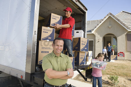 Pre teen : Family and worker unloading truck of cardboard boxes