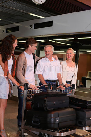 Pushing : Family arriving at the airport of their destination  pushing luggage trolleys