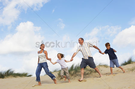 Denim : Family holding hands and running down sand dune on beach