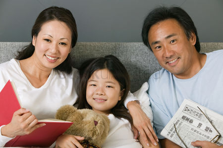 Animal head : Family relaxing together in bed reading portrait