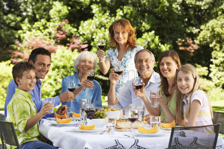 Food  beverage : Family sitting at table for lunch in back yard portrait