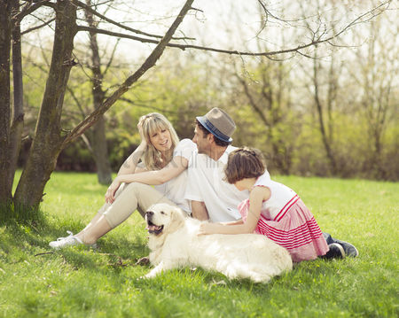 Grass : Family sitting in park with dog