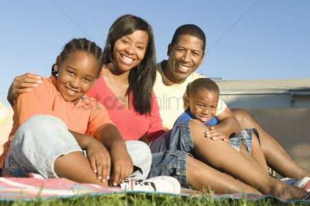 Smiling : Family sitting on grass
