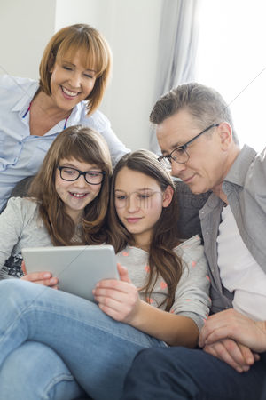Teenager : Family using digital tablet together in living room