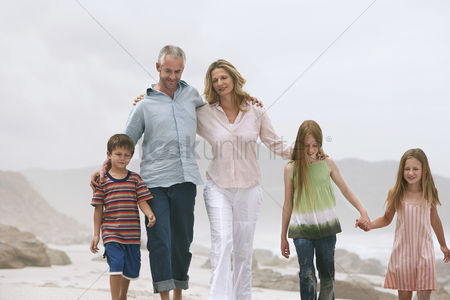 Two people : Family with three children  5-6 7-9 10-12  walking on beach