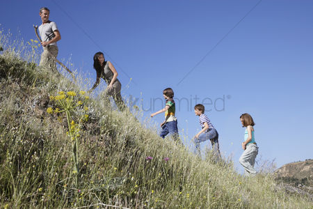 Pre teen : Family with three children  7-12  hiking side view
