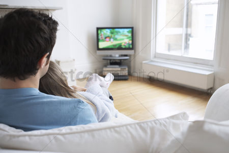 Sitting on lap : Father and daughter  5-6  watching cartoons in television back view
