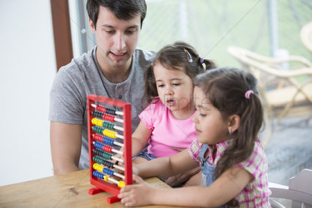Children playing : Father and daughters playing with abacus in house