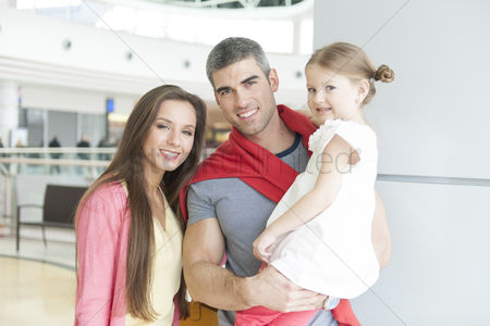 Czech republic : Father and mother pose with young daughter in shopping mall