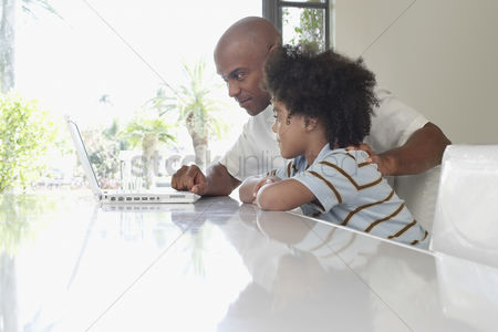 Bald : Father and son  5-6 years  using laptop on dining table side view