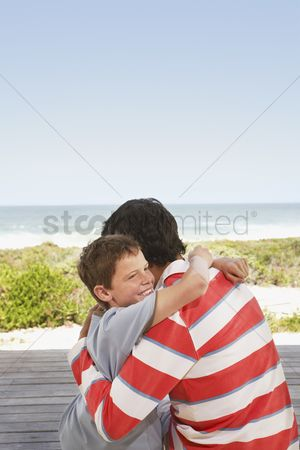 Offspring : Father and son hugging on jetty