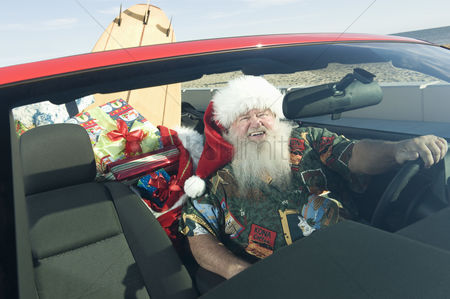 Car : Father christmas sits in red convertible with surfboard
