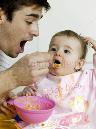 Daughter : Father feeding baby girl