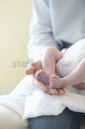 Hand : Father holding feet of two week old baby