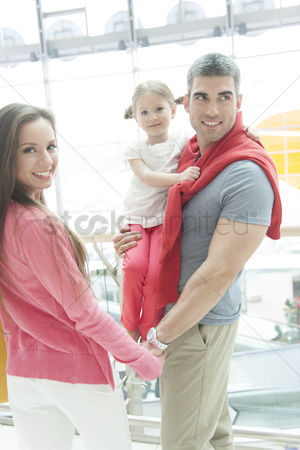Offspring : Father holding young daughter up at waist height and holding hands with mother