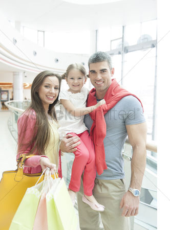 Czech republic : Father holding young girl posing with mother in shopping mall