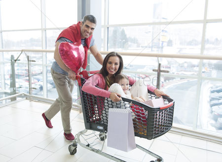 Offspring : Father pushing mother and young daughter in shopping trolley