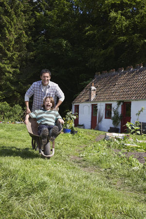 Pushing : Father pushing son  7-9  in wheelbarrow outside cottage