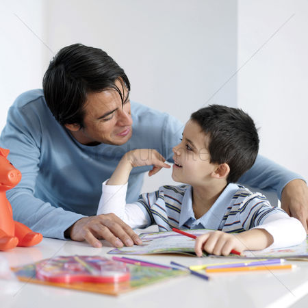 Young boy : Father watching son doing homework