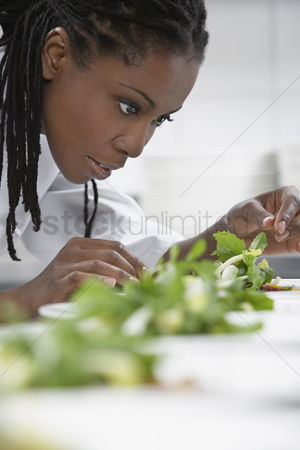 Black background : Female chef preparing salad in kitchen