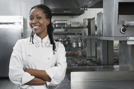Camera : Female chef with arms crossed in kitchen portrait