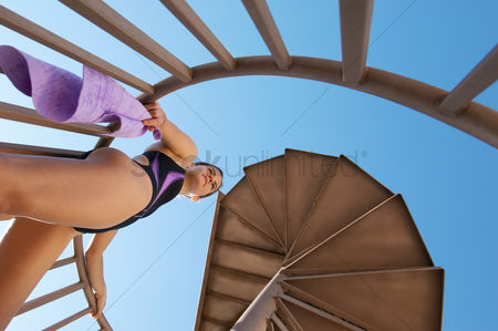 Diving : Female diver on spiral staircase to board view from below