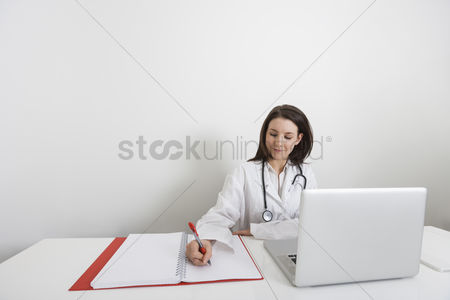 Desk : Female doctor writing on binder at desk in clinic