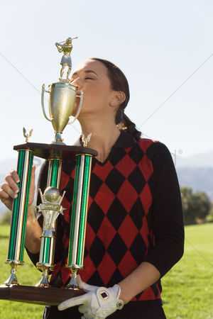 Kissing : Female golfer kissing trophy