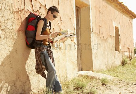 Traditional clothing : Female hiker reading map by desolate farmhouse