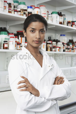 Medication : Female lab worker standing pill bottles behind